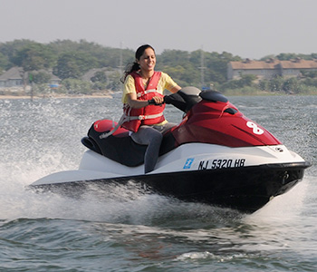 A woman in a life jacket on a personal watercraft