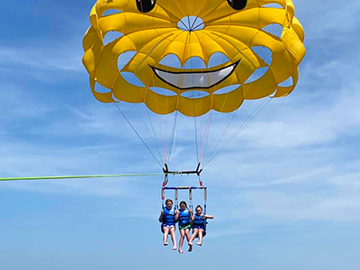 Yellow smiley-face parasail with two passengers waving over the ocean
