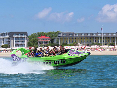 A group of people waving from a docked lime green jet boat
